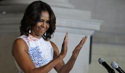 First lady Michelle Obama applauds a group of people who were just sworn in as U.S. citizens during a naturalization ceremony at the National Archives in Washington, Wednesday, June 18, 2014. (AP Photo/Susan Walsh)
