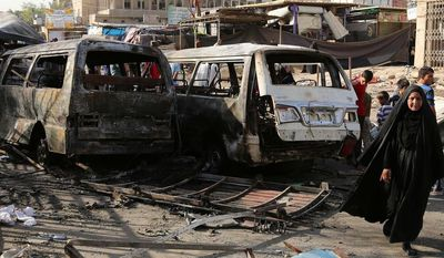 Iraqi civilians inspect damage in the aftermath of a Tuesday car bombing that killed many people and wounded tens of others in a crowded outdoor market, in Baghdad's Sadr City, Iraq, Wednesday, June 18, 2014. (AP Photo/Karim Kadim)
