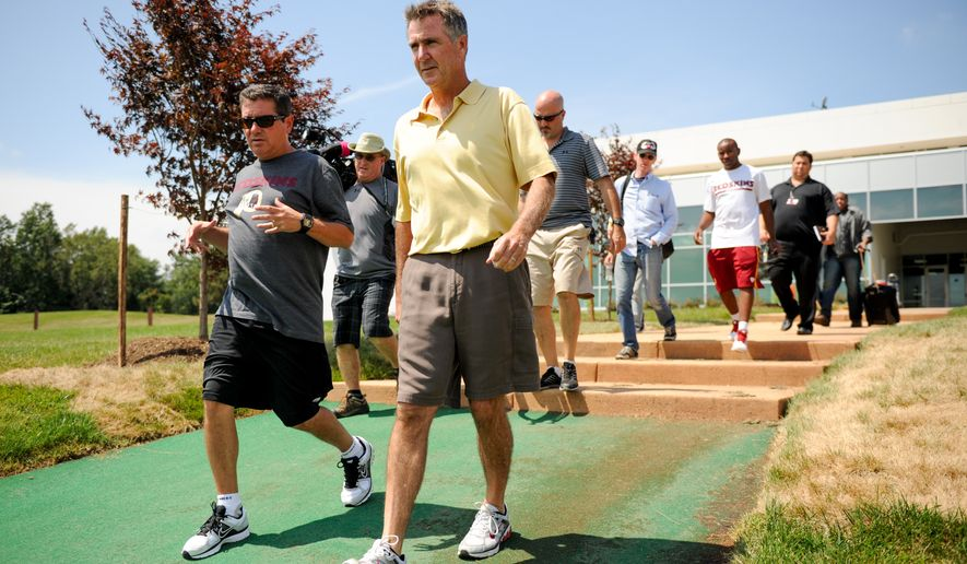 Washington Redskins owner Dan Snyder, left, and general manager Bruce Allen, center, make their way out to practice at Redskins Park, Ashburn, Va., Wednesday, August 21, 2013. (Andrew Harnik/The Washington Times)