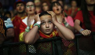 A Spanish soccer fan holds her head as she watches, on a giant display, the World Cup soccer match between Spain and Chile, in Madrid, Spain, Wednesday, June 18, 2014. (AP Photo/Andres Kudacki)