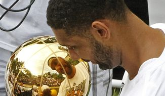 San Antonio's Tim Duncan looks at his reflection in the trophy during the Spurs' parade and celebration of their 5th NBA Championship in San Antonio, Texas, Weds.,  June 18, 2014.  (AP Photo/Michael Thomas)