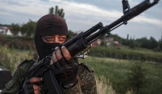 A pro-Russian fighter holds a gun during a handover of the bodies of Ukrainian troops killed in a plane shot down near Luhansk, at a check point in the village of Karlivka near Donetsk, eastern Ukraine, Wednesday, June 18, 2014. The two sides managed to arrange a brief truce Wednesday evening in the eastern town of Karlivka to allow pro-Russian forces to hand over the bodies of 49 Ukrainian troops who died when the separatists shot down a transport plane bound for the airport in Luhansk last weekend.  (AP Photo/Evgeniy Maloletka)