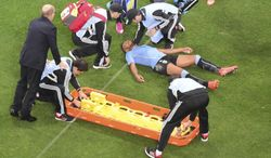 Uruguay's Alvaro Pereira is put on a stretcher during the group D World Cup soccer match between Uruguay and England at the Itaquerao Stadium in Sao Paulo, Brazil, Thursday, June 19, 2014.  (AP Photo/Francois Xavier Marit, pool)