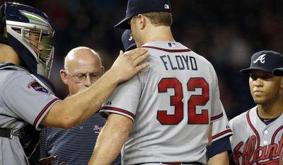 Atlanta Braves manager Fredi Gonzalez, far left, catcher Evan Gattis, head athletic trainer Jeff Porter look at starting pitcher Gavin Floyd, with shortstop Andrelton Simmons and second baseman Tommy La Stella, during the seventh inning of a baseball game against the Washington Nationals at Nationals Park Thursday, June 19, 2014, in Washington. Floyd left the game. The Braves won 3-0. Atlanta Braves right-hander Gavin Floyd left Thursday night's game against the Washington Nationals with an elbow injury in his ninth start since returning from Tommy John surgery.(AP Photo/Alex Brandon)
