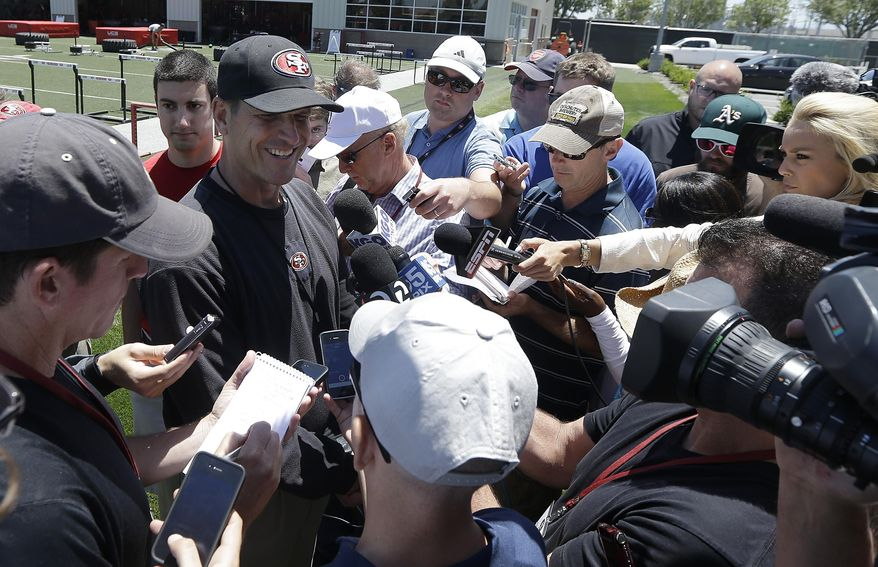 San Francisco 49ers head coach Jim Harbaugh, left, smiles while speaking to reporters during NFL football minicamp in Santa Clara, Calif., Thursday, June 19, 2014. (AP Photo/Jeff Chiu)