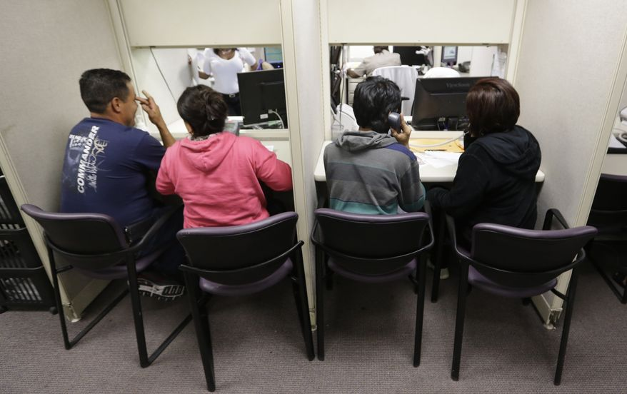 ** FILE ** This March 31, 2014, file photo shows people using a a phone bank to sign up for health care insurance at the business office of Parkland Hospital in Dallas. (AP Photo/LM Otero, File)