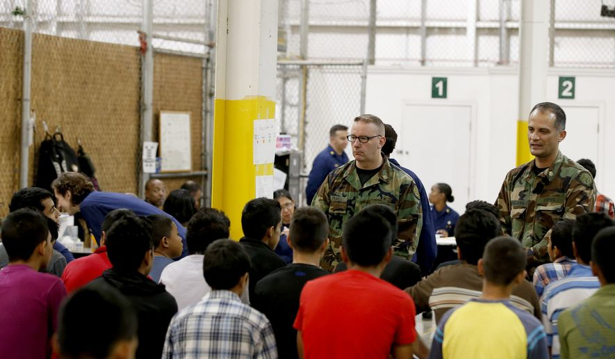 ** FILE ** In Wednesday, this June 18, 2014, file photo, boys wait for medical appointments in a holding area where hundreds of mostly Central American immigrant children were being processed and held at the U.S. Customs and Border Protection Nogales Placement Center in Nogales, Ariz. (AP Photo/Ross D. Franklin, Pool)