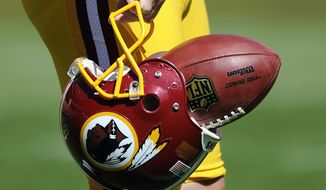 "** FILE ** In this Sept. 23, 2012, file photo, Washington Redskins punter Sav Rocca carries a football in his helmet before an NFL football game against the Cincinnati Bengals in Landover, Md. The U.S. Patent Office ruled Wednesday, June 18, 2014, that the Washington Redskins nickname is ""disparaging of Native Americans"" and that the team's federal trademarks for the name must be canceled. The ruling comes after a campaign to change the name has gained momentum over the past year. (AP Photo/Nick Wass, File)"