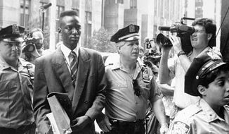 """FILE - This 1990 file photo provided by Sundance Selects shows accused rapist Yusef Salaam, second right, being escorted by police in New York in 1990. Salaam is the subject of the documentary, """"The Central Park Five,"""" about the 1989 case of five black and Latino teenagers who were convicted of raping a white woman in Central Park. A city official said Friday, June 20, 2014 that New York City has agreed to a $40 million settlement in a civil rights lawsuit filed against police and prosecutors by Salaam and four co-defendants exonerated in the notorious case of a jogger attacked in Central Park in 1989. (AP Photo/Sundance Selects, NY Daily News, File)"""