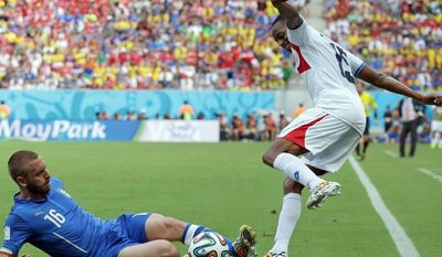 Italy's Daniele De Rossi, left, slides in to challenge Costa Rica's Junior Diaz during the group D World Cup soccer match between Italy and Costa Rica at the Arena Pernambuco in Recife, Brazil, Friday, June 20, 2014. (AP Photo/Antonio Calanni)