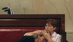 Rose Homuth of Cuba, N.Y., holds her son Brady Homuth, 25, in the Senate gallery at the Capitol as senators debate the medical marijuana bill on Friday, June 20, 2014, in Albany, N.Y. The Senate passed the bill making New York the 23rd state to legalize, but the drug won't be available for at least 18 months while regulations are written and five state-approved producers and distributors are chosen. Brady suffers from retractable seizure disorder. (AP Photo/Mike Groll)