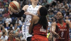 Minnesota Lynx guard Lindsey Whalen, left, goes to the basket against Washington Mystics forward Monique Currie, center, during the second quarter of a WNBA basketball game Friday, June 20, 2014, in Minneapolis. Currie was charged with a blocking foul on the play. (AP Photo/Tom Olmscheid)