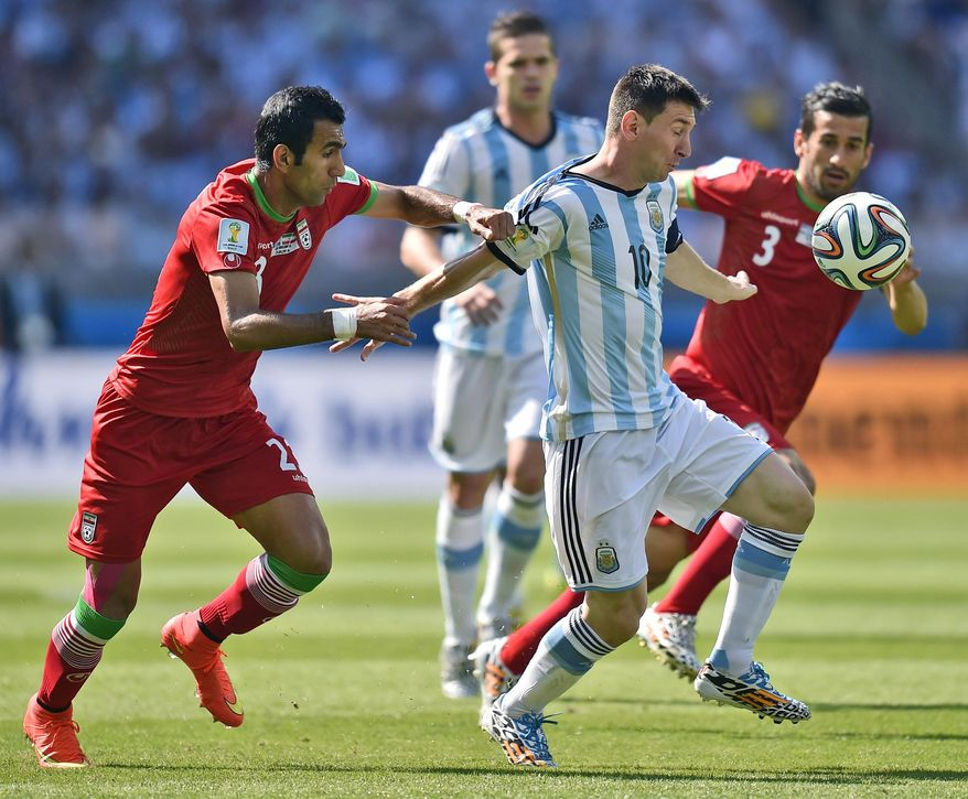 Iran's Mehrdad Pooladi, left, holds Argentina's Lionel Messi during the group F World Cup soccer match between Argentina and Iran at the Mineirao Stadium in Belo Horizonte, Brazil, Saturday, June 21, 2014. (AP Photo/Martin Meissner)