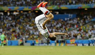 Germany's Miroslav Klose performs a flip as he celebrates after scoring his sides second goal during the group G World Cup soccer match between Germany and Ghana at the Arena Castelao in Fortaleza, Brazil, Saturday, June 21, 2014. (AP Photo/Frank Augstein)