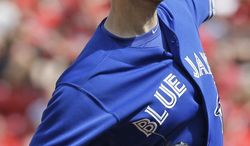 Toronto Blue Jays starting pitcher J.A. Happ throws against the Cincinnati Reds in the first inning of a baseball game, Saturday, June 21, 2014, in Cincinnati. (AP Photo/Al Behrman)