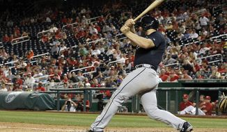 Atlanta Braves' Evan Gattis follows through on an RBI single that scored B.J. Upton for the go-ahead run during the 13th inning of a baseball game against the Washington Nationals at Nationals Park on Friday, June 20, 2014, in Washington. The Braves won 6-4 in 13 innings. (AP Photo/Alex Brandon)
