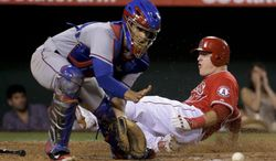 Los Angeles Angels' Mike Trout, right, scores past Texas Rangers catcher Robinson Chirinos on a hit by Josh Hamilton during the fifth inning of a baseball game in Anaheim, Calif., Friday, June 20, 2014. (AP Photo/Chris Carlson)