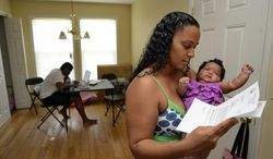 In this June 18, 2014 photo, Army Sgt. LaQuisha Gallmon, right, reads a letter from the Veterans Affairs Depart, as she holds her 2-month-old Abbagayle in Greenville, S.C. Gallmon said that her local VA office had authorized her to see a private physician during her pregnancy, so she went to an emergency room after experiencing complications in her sixth month of pregnancy. She said the VA has thus far refused to pay the resulting $700 bill. Gallmon's boyfriend Othneil Sands works on his laptop at left. (AP Photo/ Richard Shiro)
