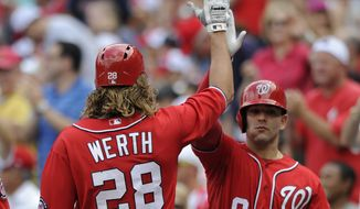 Washington Nationals' Jayson Werth (28) gets a high-five from teammate Danny Espinosa (8) after scoring on a sacrifice fly hit by Ryan Zimmerman during the first inning of a baseball game against the Atlanta Braves, Sunday, June 22, 2014, in Washington. (AP Photo/Nick Wass)
