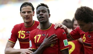 Belgium's Divock Origi, centre, celebrates with Belgium's Daniel Van Buyten, left, and Belgium's Axel Witsel, right, after Origi scored the opening goal during the group H World Cup soccer match between Belgium and Russia at the Maracana stadium in Rio de Janeiro, Brazil, Sunday, June 22, 2014. (AP Photo/Ivan Sekretarev)