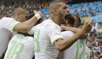 Algeria's Islam Slimani, who scored his side's first goal, celebrates with teammates after Algeria's Rafik Halliche scored the side's second goal during the group H World Cup soccer match between South Korea and Algeria at the Estadio Beira-Rio in Porto Alegre, Brazil, Sunday, June 22, 2014. (AP Photo/Lee Jin-man)