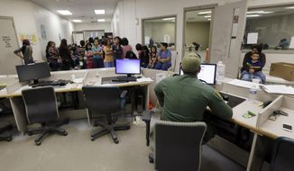 This June 18, 2014, file photo shows U.S. Customs and Border Protection agents work at a processing facility in Brownsville, Texas. (AP Photo/Eric Gay, Pool) ** FILE **