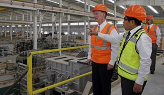 ** FILE ** In this Aug. 29, 2013, photo provided by the Alabama Governor's office, Gov. Robert Bentley, left, listens to Roger Zhang, Golden Dragon U.S.A. president, during a tour of the new Golden Dragon copper tubing plant, then under construction, in Pine Hill, Ala. Golden Dragon, the first company Bentley recruited to Alabama after being elected, will employ 300 new full-time employees in rural Wilcox County. (AP Photo/Alabama Governor's Office, Jamie Martin)