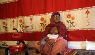 In this June 5, 2014 photo, Somali refugee Hasna Abdi, 26, holds her child Muridi Hassan, 1, as he falls asleep after a bottle feeding in the main room of their apartment in Springfield, Mass. Springfield Mayor Domenic Sarno is calling for an end to refugee resettlement in his city, saying Somali families are putting pressure on already strained services. (AP Photo/Stephan Savoia)