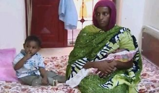 FILE - In this file image made from an undated video provided Thursday, June 5, 2014, by Al Fajer, a Sudanese nongovernmental organization, Meriam Ibrahim, sitting next to Martin, her 18-month-old son, holds her newborn baby girl that she gave birth to in jail last week, as the NGO visits her in a room at a prison in Khartoum, Sudan. Sudan's official news agency, SUNA, said the Court of Cassation in Khartoum on Monday, June 23, canceled the death sentence against 27-year-old Meriam Ibrahim after defense lawyers presented their case. The court ordered her release. (AP Photo/Al Fajer, File)