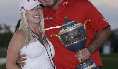 Patrick Reed poses with his wife Justine and The Gene Sarazen Cup after winning the Cadillac Championship golf tournament Sunday, March 9, 2014, in Doral, Fla. (AP Photo/Wilfredo Lee)