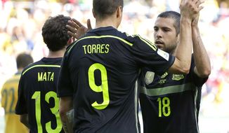 Spain's Fernando Torres, center, celebrates with teammate Jordi Alba after scoring during the group B World Cup soccer match between Australia and Spain at the Arena da Baixada in Curitiba, Brazil, Monday, June 23, 2014. (AP Photo/Fernando Vergara)