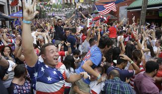 Fans cheer after the United States scored a goal against Portugal as they watch a World Cup soccer match on a big screen television Sunday, June 22, 2014, in Orlando, Fla. (AP Photo/John Raoux)
