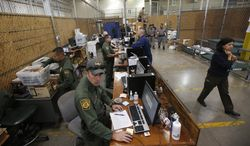 """FILE - This June 18, 2014 file-pool photo shows U.S. Customs and Border Protection officers waiting for new arrivals in the intake area where hundreds of mostly Central American immigrant children are being processed and held at the U.S. Customs and Border Protection Nogales Placement Center in Nogales, Ariz. The Obama administration has released into the U.S. an untold number of immigrant families caught traveling illegally from Central America in recent months _ and although the government knows how many it's released, it won't say publicly. Senior U.S. officials directly familiar with the issue, including at the Homeland Security Department and White House, have so far dodged the answer on at least seven occasions over two weeks, alternately saying that they did not know the figure or didn't have it immediately at hand. """"We will get back to you,"""" the Homeland Security deputy secretary said Friday.  (AP Photo/Ross D. Franklin, File-Pool)"""