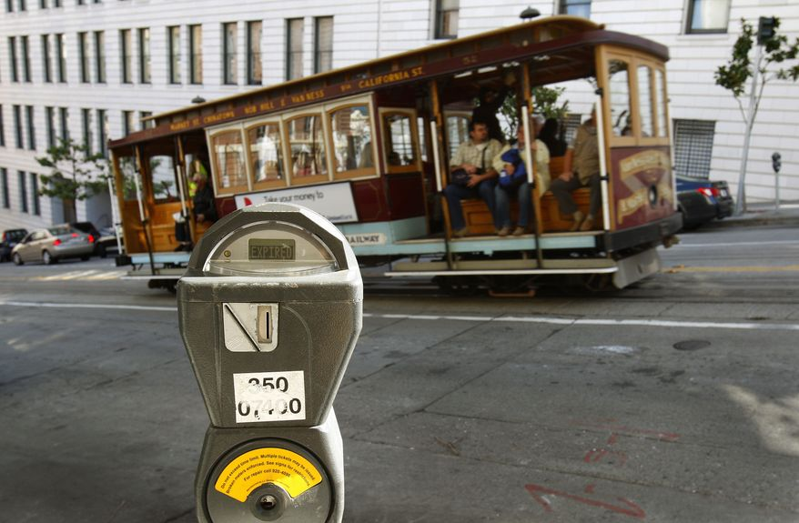 FILE - In this Oct. 27, 2009 file photo, a cable car passes a parking meter near San Francisco's financial district. San Francisco City Attorney Dennis Herrera on Monday, June 23, 2014 issued a cease-and-desist demand to a mobile app called Monkey Parking, which allows people to auction off public parking spaces that they're using to other nearby drivers. (AP Photo/Ben Margot, File)