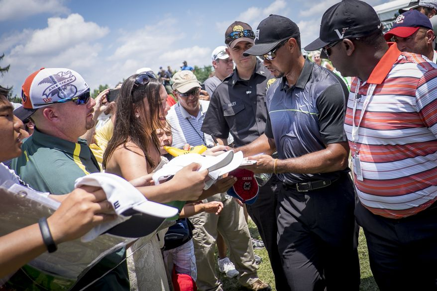 Tiger Woods signs autographs for fans as he leaves the practice tee Tuesday at the Quicken Loans National golf tournament at Congressional Country Club in Bethesda, Maryland. Photo: Pete Marovich Special to The Washington Times