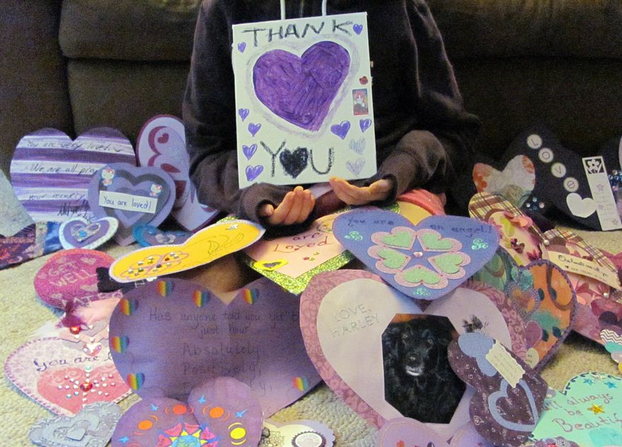 """In this June 19, 2014, photo provided by Dana Hoffmann, a 12-year-old Waukesha, Wis., girl who wished to remain unidentified, holds a """"Thank You"""" poster for the many supporters from around the world that have sent her cards. (AP Photo/Dana Hoffmann)"""