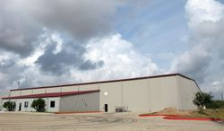 A corrugated steel warehouse is shown Tuesday, June 24, 2014, in McAllen, Texas, that the U.S. government plans to turn into a processing facility for unaccompanied children who have entered the country illegally, according to construction permits. The permits show plans for four fence-enclosed pods inside the warehouse that could eventually accommodate about 1,000 children. The Border Patrol has been overwhelmed by more than 52,000 unaccompanied minors that have been arrested since October 2013, after entering the Unites States illegally. (AP Photo/Christopher Sherman)