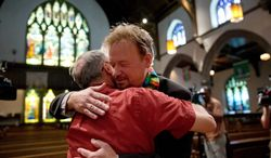 United Methodist pastor Frank Schaefer, right, hugs the Rev. David Wesley Brown after a news conference Tuesday, June 24, 2014, at First United Methodist Church of Germantown in Philadelphia. Schaefer, who presided over his son's same-sex wedding ceremony and vowed to perform other gay marriages if asked, can return to the pulpit after a United Methodist Church appeals panel on Tuesday overturned a decision to defrock him. (AP Photo/Matt Rourke)