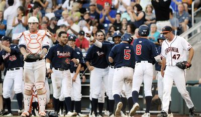 Virginia catcher Nate Irving, left, and pitcher Whit Mayberry (47) stand near as the Vanderbilt bench celebrates in the third inning of the opening game of the best-of-three NCAA baseball College World Series finals in Omaha, Neb., Monday, June 23, 2014. (AP Photo/Eric Francis)