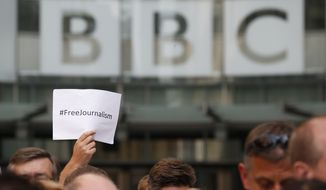 BBC journalists and staff, hold a minute of silence in support of the jailed journalists in Egypt, exactly 24 hours after their sentencing, outside the BBC headquarters in central London, Tuesday, June 24, 2014. An Egyptian court on Monday convicted three journalists from Al-Jazeera English and sentenced them to seven years in prison each on terrorism-related charges, bringing widespread criticism that the verdict was a blow to freedom of expression. The three, Australian Peter Greste, Canadian-Egyptian Mohamed Fahmy and Egyptian Baher Mohammed, have been detained since December charged with supporting the Muslim Brotherhood, which has been declared a terrorist organization, and of fabricating footage to undermine Egypt's national security and make it appear the country was facing civil war. (AP Photo/Lefteris Pitarakis)