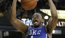 FILE - In this March 5, 2014 film photo, Duke's Jabari Parker (1)  dunks against Wake Forest during the second half of an NCAA college basketball game in Winston-Salem, N.C. Parker is a possible pick in the 2014 NBA Draft, Thursday, June 26, 2014 in New York.(AP Photo/Chuck Burton, File)