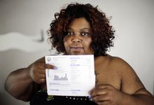 Nicole Hill holds up her past due water bill at her home in Detroit Wednesday, June 25, 2014. Detroit Water department spokeswoman Curtrise Garner says service to 4,500 customers was cut last month, but more than half then paid up. Garner says about $90 million is owed by 90,000 active customers who are behind at least two months. United Nations experts say water shutoffs at Detroit homes due to overdue bills violate international human rights. (AP Photo/Paul Sancya)