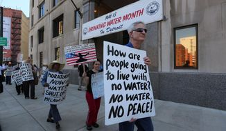 """This photo taken May 30, 2014, shows protesters with Moratorium Now! along with about 30 people rallying outside the Detroit Water Department on Randolph street against water shut-offs. The group chanted """"Water is a human right"""". (AP Photo/Detroit Free Press, Jessica J. Trevino)"""