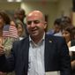 Karzan Mahmoud, an Iraqi native, waves the flag after taking the oath to become a U.S. citizen along with 50 others at a naturalization ceremony in Fairfax, Virginia. (Khalid Naji-Allah/Special to The Washington Times)