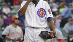 Chicago Cubs starter Edwin Jackson wipes his face after Cincinnati Reds' Joey Votto walked to first base during the first inning of a baseball game in Chicago, Wednesday, June 25, 2014. (AP Photo/Nam Y. Huh)