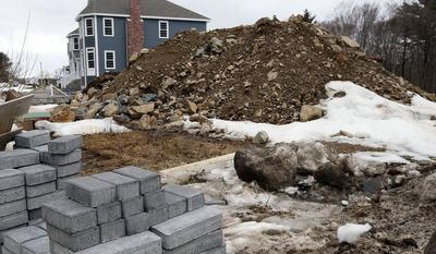 FILE - In this Friday, March 21, 2014, file photo, snow partially covers the ground where a single family housing construction is underway in North Andover, Mass. Craig Alexander, chief economist at TD Bank, estimates that the brutal winter slowed economic activity by about 1.5 percentage points on an annual basis. (AP Photo/Elise Amendola, File)