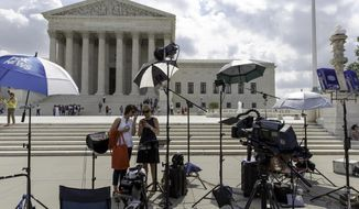News media crews wait for decisions in the final days of the Supreme Court's term, Wednesday, June 25, 2014, in Washington. The justices ruled Wednesday that a startup Internet company has to pay broadcasters when it takes television programs from the airwaves and allows subscribers to watch them on smartphones and other portable devices. The justices said by a 6-3 vote that Aereo Inc. is violating the broadcasters' copyrights by taking the signals for free.  (AP Photo/J. Scott Applewhite)