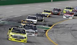 Pole-sitter Kyle Busch (51) leads the field into the second lap of the NASCAR Trucks auto race at Kentucky Speedway in Sparta, Ky., Thursday June 26, 2014. (AP Photo/Garry Jones)