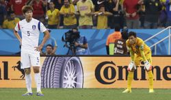 South Korea's Kim Young-gwon, left, and  goalkeeper Kim Seung-gyu pause after Belgium's Belgium's Jan Vertonghen (not shown) scored the first goal of the group H World Cup soccer match between South Korea and Belgium at the Itaquerao Stadium in Sao Paulo, Brazil, Thursday, June 26, 2014. (AP Photo/Lee Jin-man)