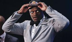 Kentucky forward Julius Randle dons a Los Angeles Lakers cap after being selected seventh overall by the Lakers during the 2014 NBA draft, Thursday, June 26, 2014, in New York.  (AP Photo/Jason DeCrow)